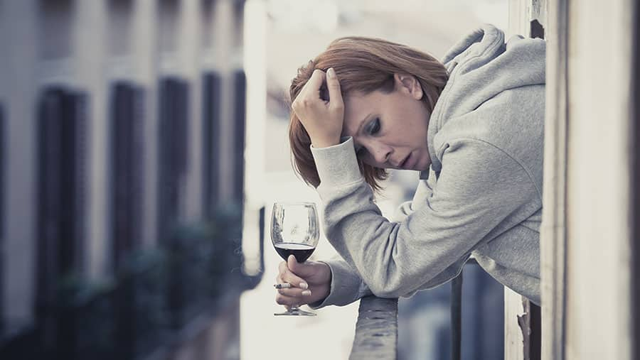 Woman with dementia holds a glass of wine and grabs her head as she struggles to remember something, showing connection between alcohol and dementia.