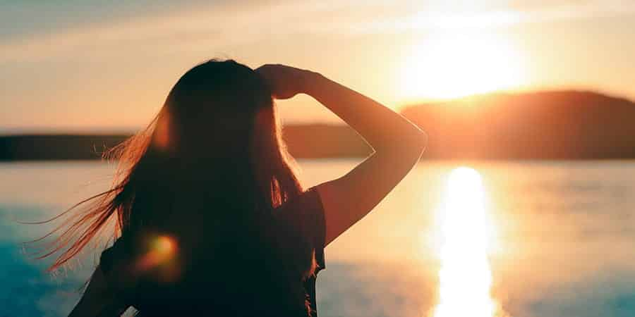 Women at inpatient rehab for addiction watches sunset over the ocean