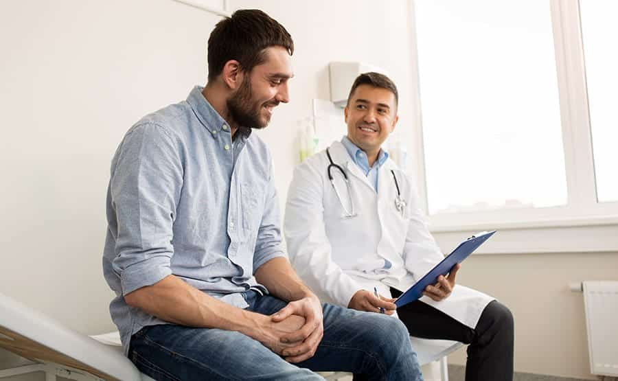 Addict sits and reviews his chart with medical rehab doctor after arriving at his affordable treatment center.