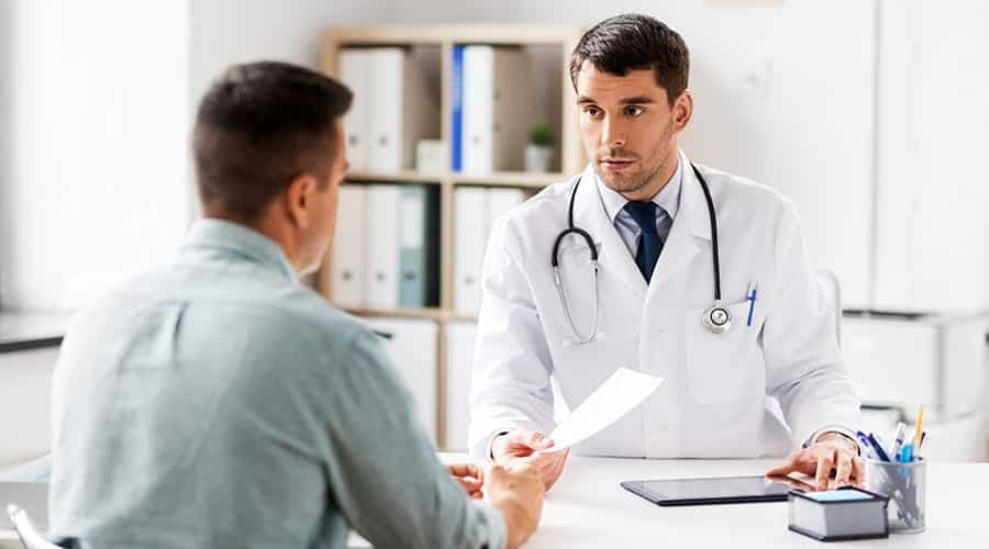 Doctor sits with client in detox after examination to address medical conditions and ensure the full client is treated