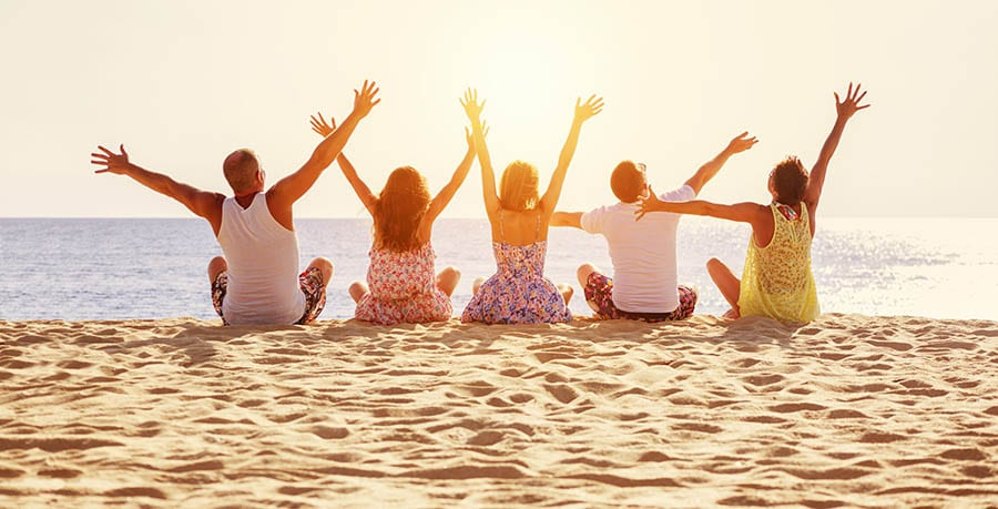 Friends in addiction rehab together sitting on the sand celebrating their recovery.