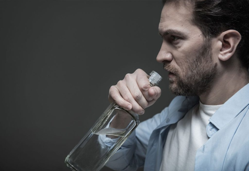 The connections between addiction, grief, and loss shown by man drinking alcohol and grieving.