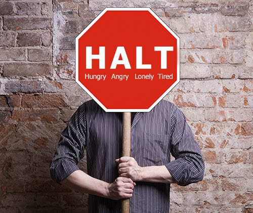 Man holding HALT: Hungry, Angry, Lonely, Tired sign in front of his face, showing the meaning of HALT.