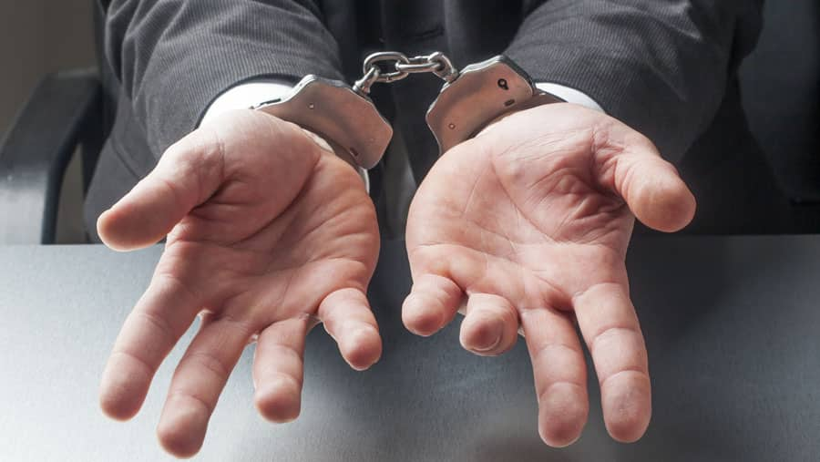 Handcuffs on wrists of man for drug usage: Incarceration Vs. Rehabilitation