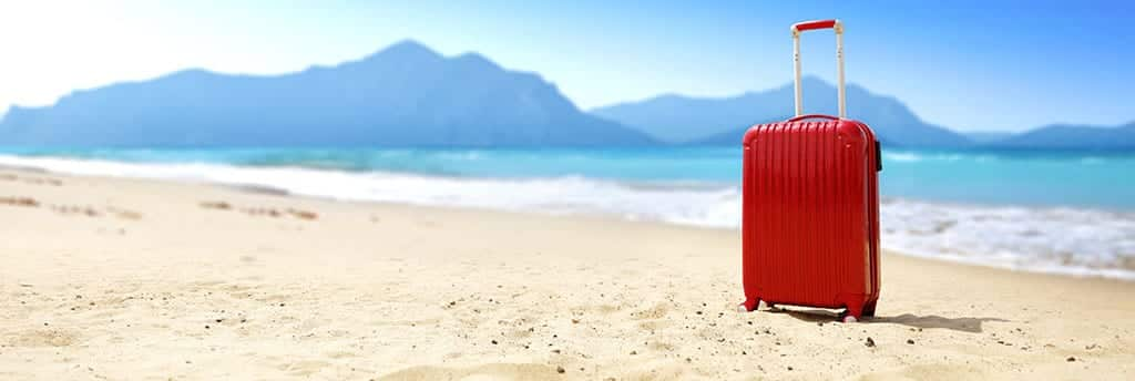Red suitcase left on beautiful beach at inpatient rehab treatment facility for drug addiction