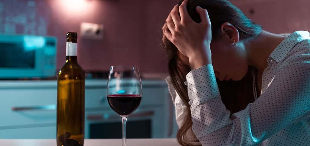 Problem Drinking - depressed woman drinking alcohol alone