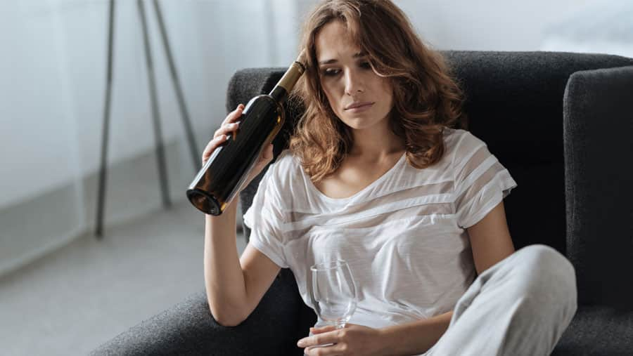 A woman holds a bottle of wine and an empty wineglass, pausing to reconsider rehab addiction treatment.