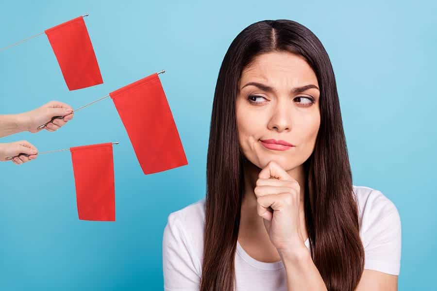 Woman looks suspiciously at three red flags; learning how to find the best drug rehab.