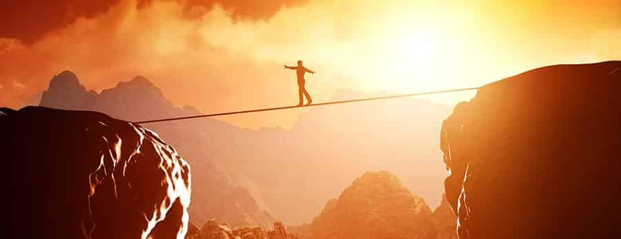 Person walks across gap on tightrope, showing change can be uncomfortable or even scary, but drug treatment is worth it.