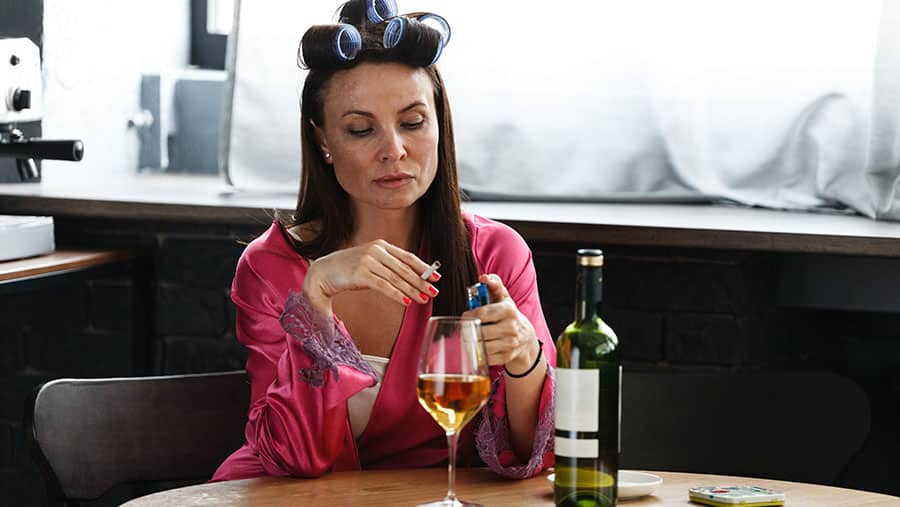 A mother sits in nightgown during the day with a glass of wine and a cigarette - showing she may have a problem with alcohol addiction.