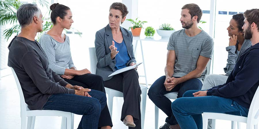A group of parents all in recovery discuss their recovery from drugs and alcohol in a group setting.