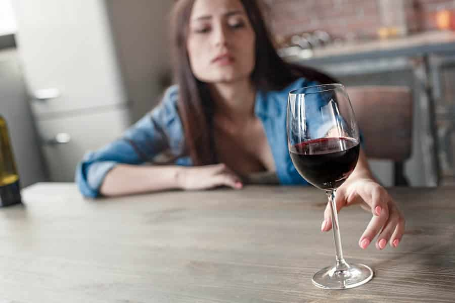 An intoxicated woman binge drinking reaches across the table for another glass of wine.