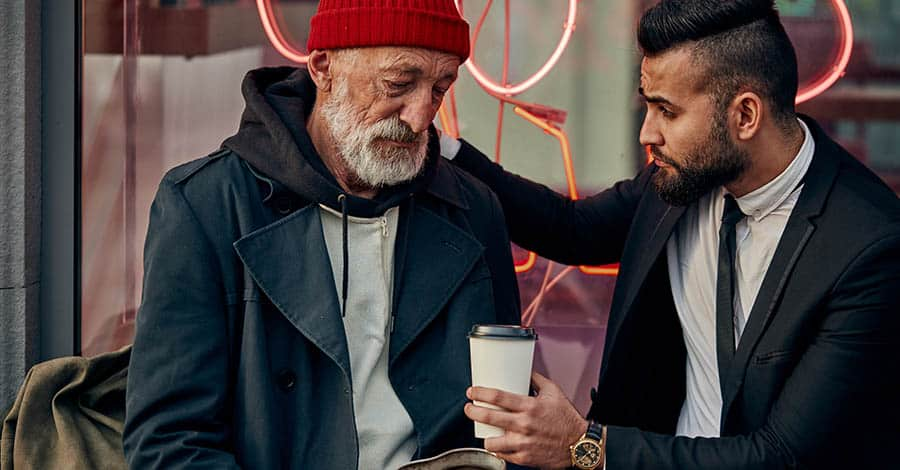Man in suit gives homeless man a hot cup of coffee, showing compassion for drug addiction is a big part of harm reduction.