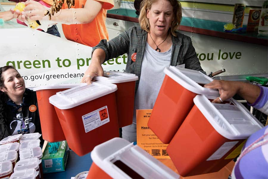 People drop off used Injection needles and pick up free sharps disposal containers at an event in Portland, OR.