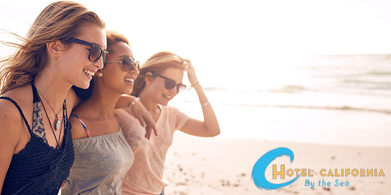 Three happy women who quit drinking alcohol in treatment walk along the beach smiling.