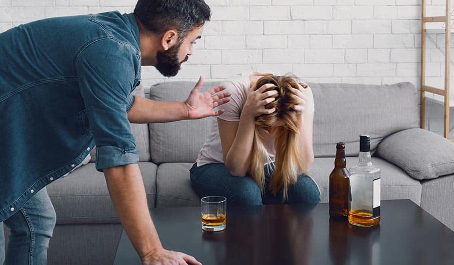 Woman holds her hands on head after drinking too much. Evidence shows women are more sensitive to the effects of alcohol.